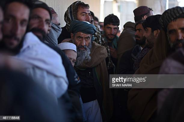 Afghan displaced men line up to receive winter supplies at a UNHCR distribution centre for needy refugees at the Women's Garden in Kabul on January 7...