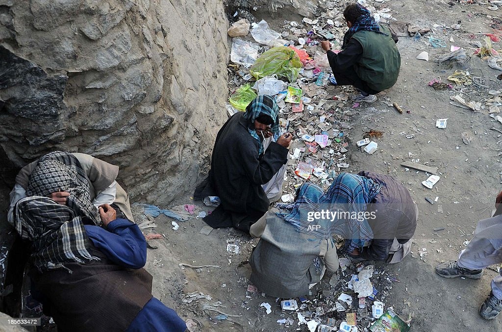 Afghan drug addicts huddle together as they use drugs alongside the river in the old part of Kabul on October 23, 2013. Afghanistan produces 90 percent of all opiate drugs in the world, but only recently became a major consumer - out of a population of 35 million, more than a million are addicted to drugs today. AFP PHOTO/Noorullah SHIRZADA