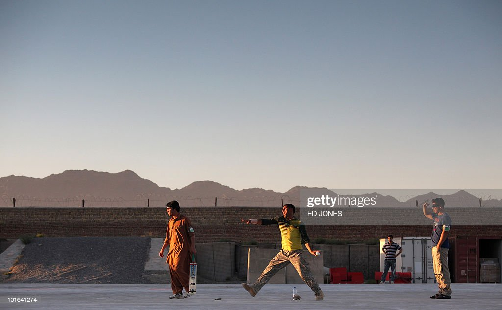 Afghan employees at the NATO camp in Kandahar play cricket at the base on June 5, 2010. As well as the continued training of Afghan security forces, the US and NATO are boosting the number of foreign troops in Afghanistan to 150,000 by August 2010 as they build up operations to beat back the Taliban from around their spiritual home of Kandahar in the south.