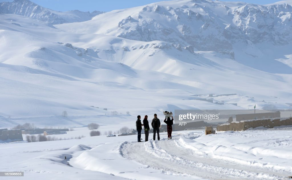 Afghan ethnic Hazara villagers look on as a woman carries some dishes while walking along a snow covered road on the outskirts of Bamiyan on March 1, 2013. Bamiyan, some 200 kilometres (124 miles) northwest of Kabul, stands in a deep green and lush valley stretching 100 kilometres through central Afghanistan, on the former Silk Road that once linked China with Central Asia and beyond. The town was home to two nearly 2,000-year-old Buddha statues before they were destroyed by the Taliban, months before their regime was toppled in a US-led invasion in late 2001. AFP PHOTO / Massoud HOSSAINI