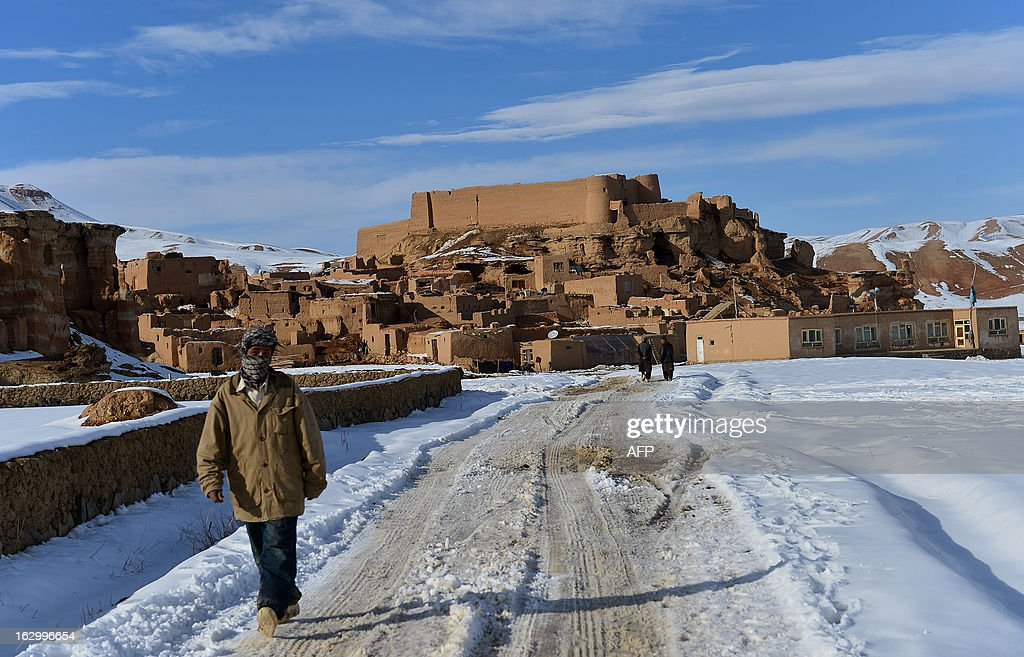 Afghan ethnic Hazara villagers walk along a snow covered road on the outskirts of Bamiyan on March 1, 2013. Bamiyan, some 200 kilometres (124 miles) northwest of Kabul, stands in a deep green and lush valley stretching 100 kilometres through central Afghanistan, on the former Silk Road that once linked China with Central Asia and beyond. The town was home to two nearly 2,000-year-old Buddha statues before they were destroyed by the Taliban, months before their regime was toppled in a US-led invasion in late 2001. AFP PHOTO / Massoud HOSSAINI