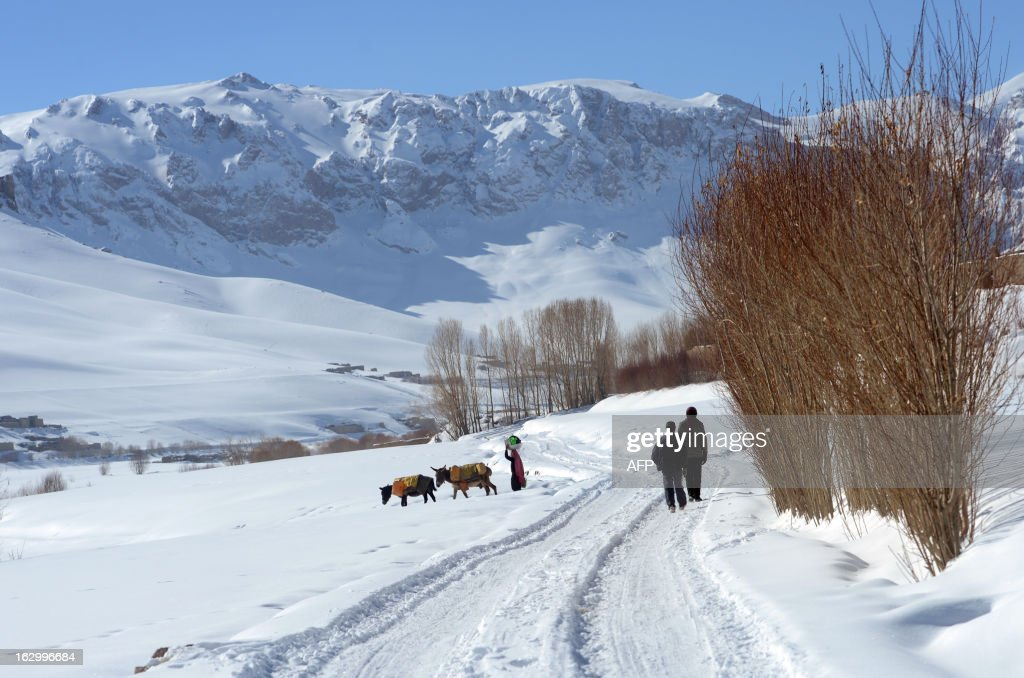 Afghan ethnic Hazara villagers walk as a woman (L) carries some dishes on the outskirts of Bamiyan on March 1, 2013. Bamiyan, some 200 kilometres (124 miles) northwest of Kabul, stands in a deep green and lush valley stretching 100 kilometres through central Afghanistan, on the former Silk Road that once linked China with Central Asia and beyond. The town was home to two nearly 2,000-year-old Buddha statues before they were destroyed by the Taliban, months before their regime was toppled in a US-led invasion in late 2001. AFP PHOTO / Massoud HOSSAINI
