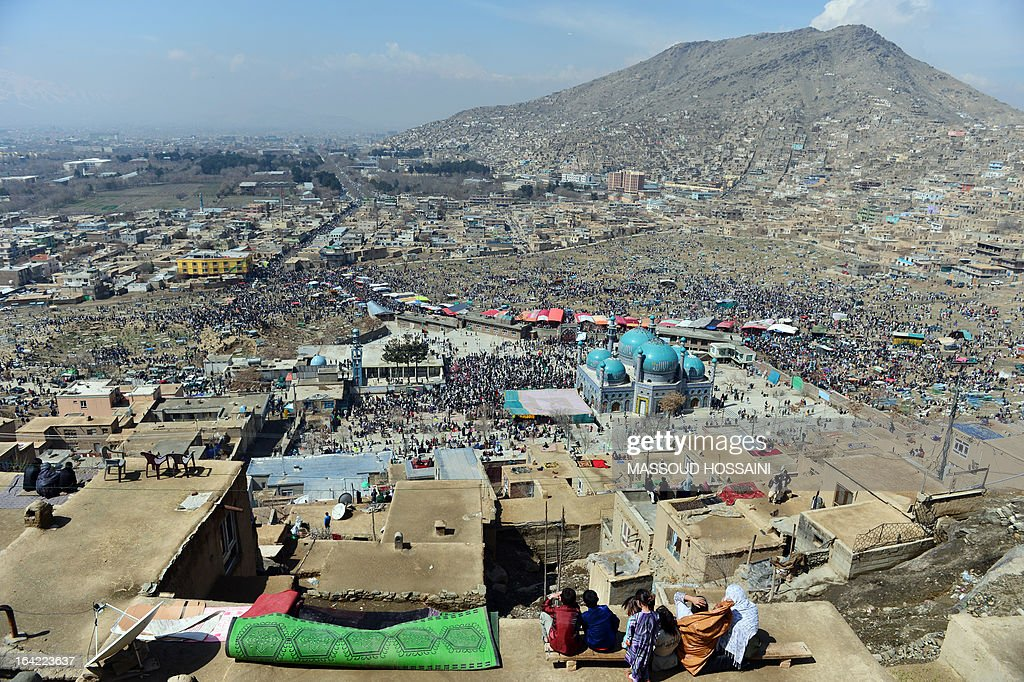 Afghan families gather on top of their home's roof near Sakhi shrine, the centre of the Afghanistan new year celebrations in Kabul during Nowruz festivities on March 21, 2013. Nowruz, one of the biggest festivals of the war-scarred nation, marks the first day of spring and the beginning of the year in the Persian calendar. Nowruz is calculated according to a solar calendar, this coming year marking 1392. AFP PHOTO / Massoud HOSSAINI