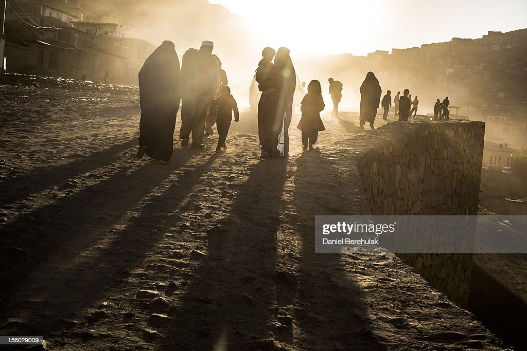 Afghan families walk along a dusty road on November 11, 2012 in Kabul, Afghanistan.