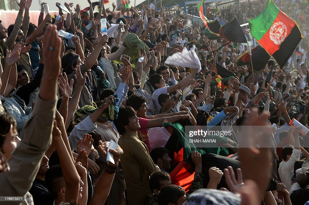 Afghan fans celebrate their team's first goal during the match between Afghanistan and Pakistan at the Afghanistan Football Federation (AFF) stadium in Kabul on August 20, 2013. Afghanistan's football team sparked rowdy celebrations across the war-battered nation on August 20 after securing an convincing 3-0 win over arch-rivals Pakistan in the first international match in Kabul for ten years. AFP PHOTO/ SHAH Marai