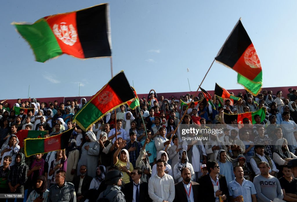 Afghan fans fan wave the national flag as they celebrate their team's first goal against Pakistan at the Afghanistan Football Federation (AFF) stadium in Kabul on August 20, 2013. Afghanistan's football team sparked rowdy celebrations across the war-battered nation on August 20 after securing an convincing 3-0 win over arch-rivals Pakistan in the first international match in Kabul for ten years. AFP PHOTO/ SHAH Marai