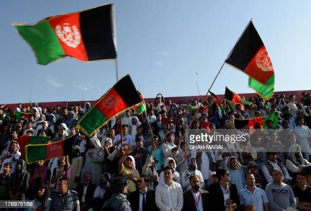 Afghan fans fan wave the national flag as they celebrate their team's first goal against Pakistan at the Afghanistan Football Federation stadium in...