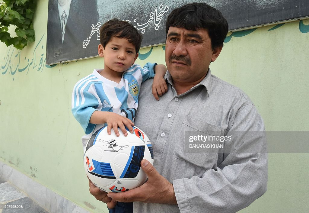 Afghan father Mohammad Arif Ahmadi holds his son Murtaza, 5, and a fan of football player Lionel Messi, as he speaks during an interview with AFP in Pakistan's southwestern city of Quetta on May 3, 2016. The young Afghan boy who captivated hearts after he was pictured wearing a plastic bag as an improvised Lionel Messi jersey has appealed to the UN refugee agency after fleeing Afghanistan. Murtaza Ahmadi became an Internet sensation in January after his older brother posted the picture on Facebook, with the Argentine superstar sending autographed jerseys to his tiny fan via UNICEF. KHAN
