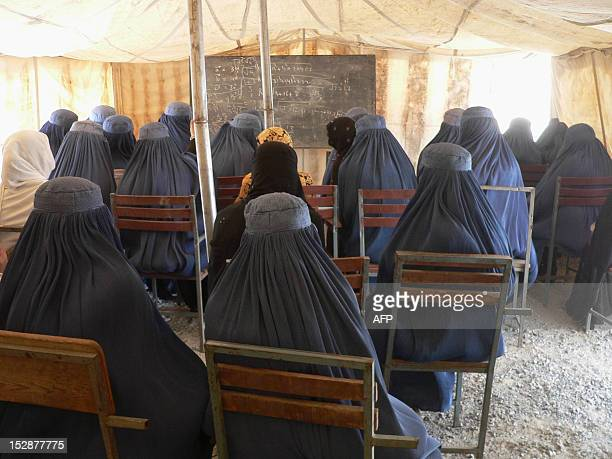 Afghan female university students attend a math class under a tent at the Nangarhar University campus in Jalalabad on September 28 2012 The students...