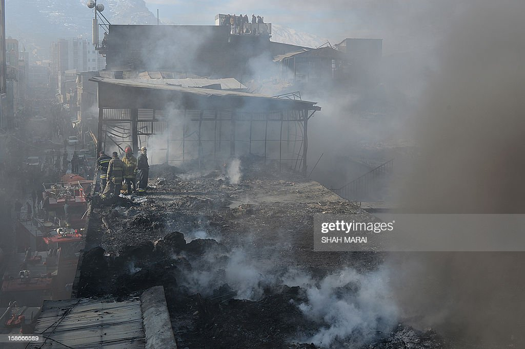 Afghan firefighters and local volunteers salvage goods from shops after a huge fire swept through a market in Kabul on December 23, 2012. A huge fire swept through a market in downtown Kabul on December 23, destroying hundreds of shops and forcing the city's nearby money exchange to evacuate, police and witnesses said. There were no reports of any casualties in the early morning blaze which destroyed most of the cloth market's 500 shops, Kabul fire department officials told AFP. AFP PHOTO/ SHAH Marai
