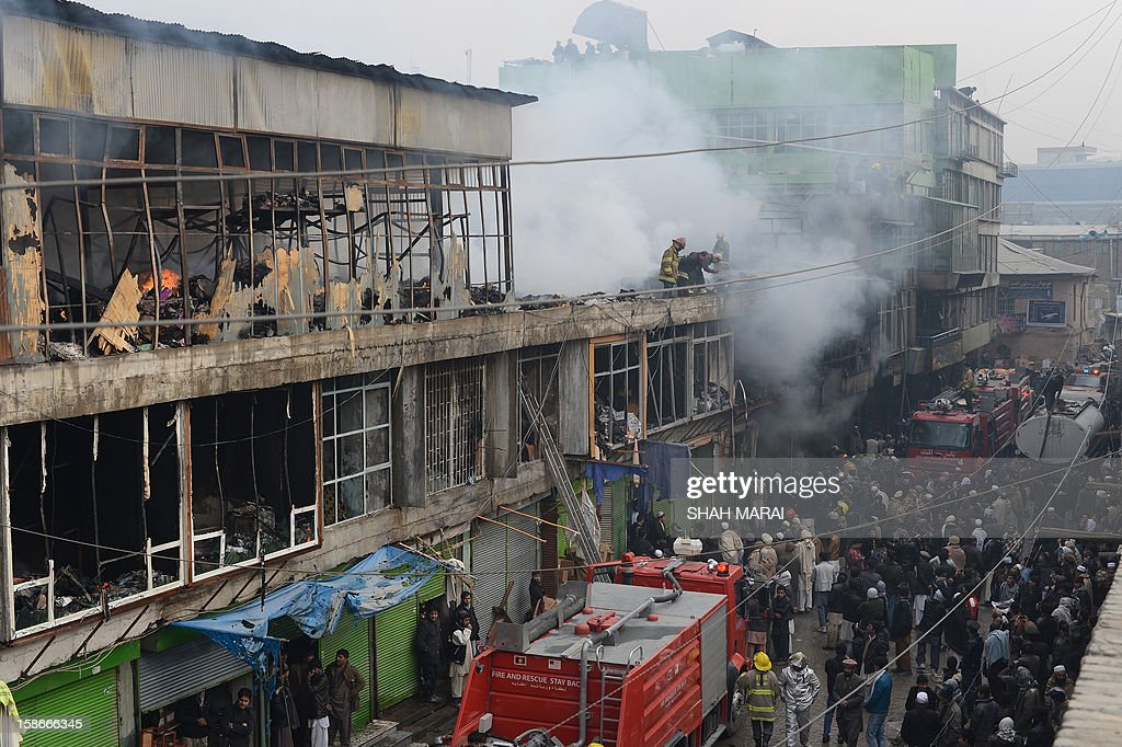 Afghan firefighters and onlookers are pictured at the scene after a huge fire swept through a market in Kabul on December 23, 2012. A huge fire swept through a market in downtown Kabul on December 23, destroying hundreds of shops and forcing the city's nearby money exchange to evacuate, police and witnesses said. There were no reports of any casualties in the early morning blaze which destroyed most of the cloth market's 500 shops, Kabul fire department officials told AFP. AFP PHOTO/ SHAH Marai