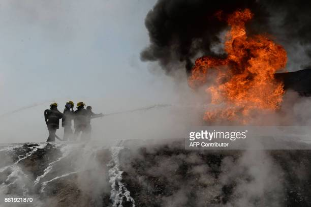 Afghan firefighters attempt to extinguish a burning fuel tanker which was exploded by a magnetic bomb on the outskirts of Jalalabad on October 16...