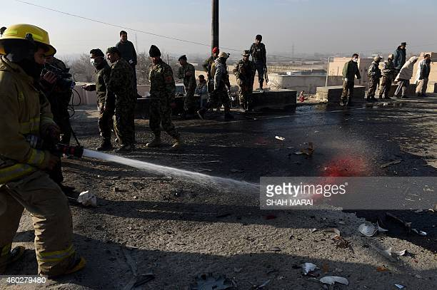 Afghan firefighters clean the road at the site of a suicide bombing in Kabul on December 11 2014 A Taliban suicide blast claimed killed at least six...
