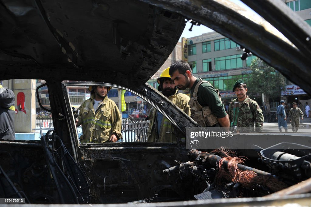 Afghan firefighters stand near a vehicle after a blast in Jalalabad on September 1, 2013. A magnetic bomb was attached to the vehicle f Nangarhar mayor, Lal Agha Kakar, wounding the driver when it detonated, Ahmad Zia Abdulzai, Nangarhar governor spokesman told AFP. AFP PHOTO/ Noorullah SHIRZADA
