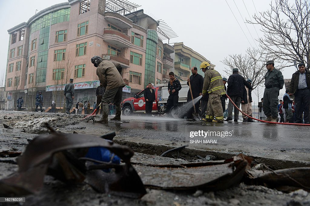 Afghan firefighters wash debris off the road following a suicide attack against a bus carrying Afghan army personnel in Kabul on February 27, 2013. A Taliban suicide bomber attacked a bus carrying Afghan army personnel in Kabul on February 27, wounding six people and highlighting a growing trend of strikes on Afghan rather than NATO military targets. AFP PHOTO/ SHAH Marai