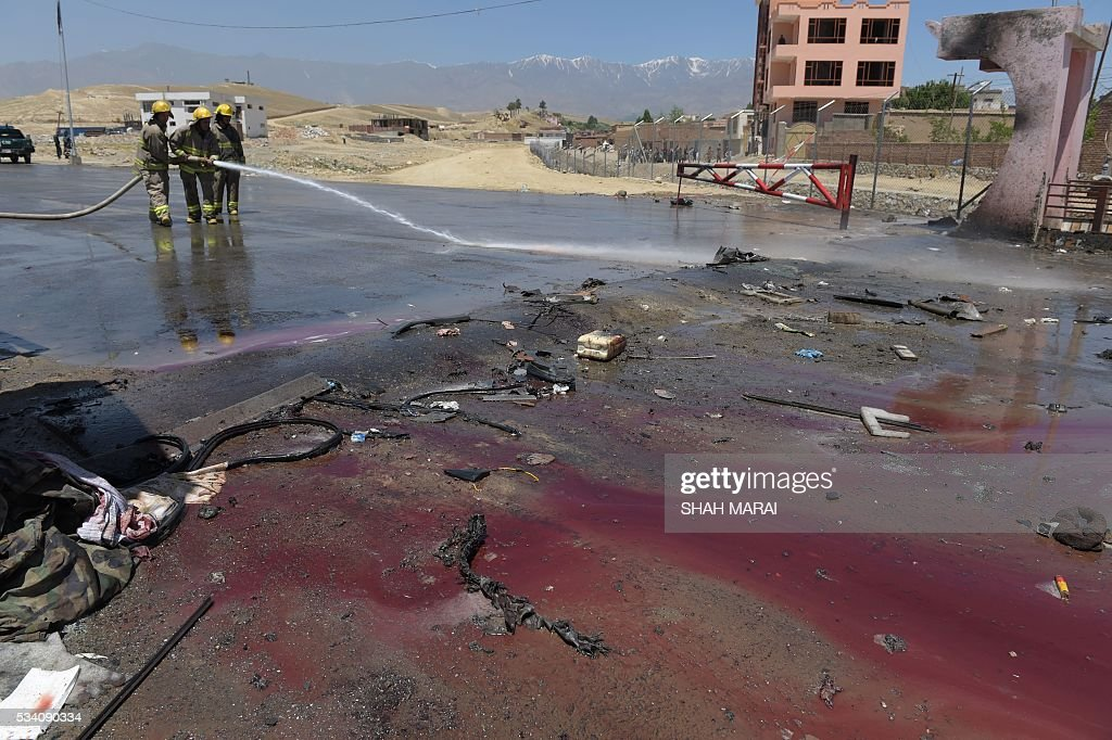 Afghan firefighters wash the road at the scene of a suicide bomb attack in Paghman district in Kabul on May 25, 2016. Ten people were killed in Afghanistan on May 25 when a suicide bomber on foot detonated his explosives, striking a vehicle carrying court employees near the capital Kabul, the interior ministry said. 'A suicide bomber blew himself up... in Paghman district, killing 10 people and wounding four others,' ministry spokesman Najib Danish told AFP. / AFP / SHAH