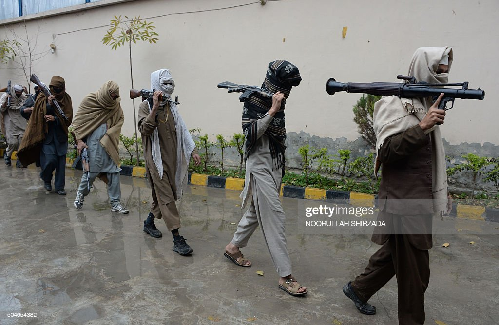 Afghan former Taliban fighters carry their weapons before handing them over as part of a government peace and reconciliation process at a ceremony in...