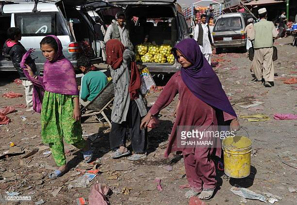 Afghan girls collect rotten apples at the vegetable market in Kabul on October 12 2010 Afghanistan is one of the world's poorest countries where...