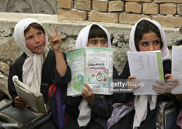 Afghan girls listen during Dari class in a partially constructed open air classroom May 30 2005 at a school in Faisabad in the Badakhshan district...