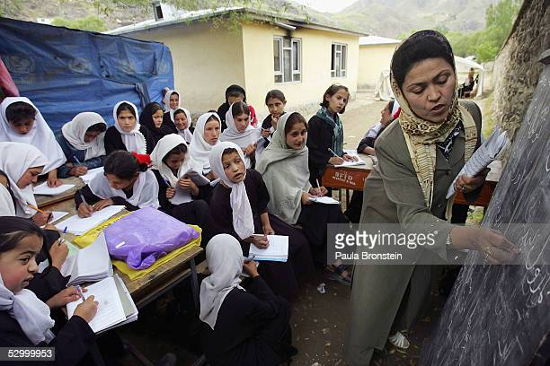 Afghan girls listen during language class in an open air classroom after space ran out May 30 2005 at a school in Faisabad in the Badakhshan district...
