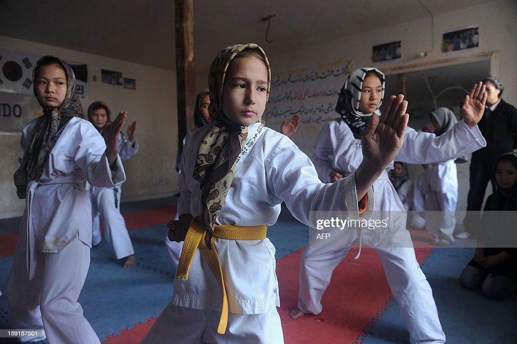 Afghan girls practice Taekwondo moves during a martial arts class in Herat on January 9, 2013. The Taliban regime that was forced from power eleven years ago did not allow women and girls to play sports as part of a raft of measures that kept them uneducated and out of the public domain. AFP PHOTO /Aref Karimi