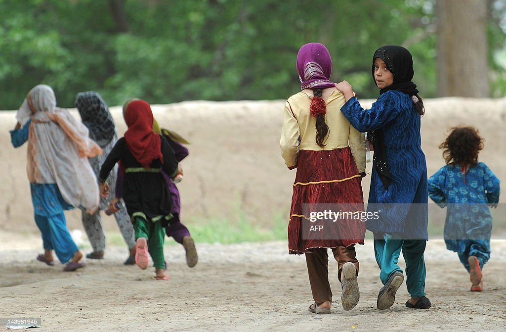Afghan girls run down a lane in the city of Mazari Sharif capital of Balkh province on May 6 2012 Mazari Sharif is the capital of Balkh province with...
