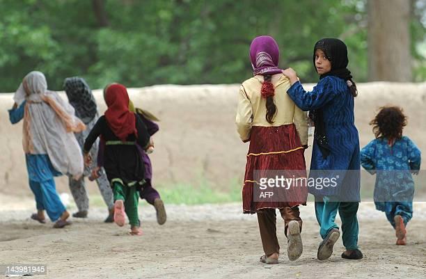 Afghan girls run down a lane in the city of Mazari Sharif capital of Balkh province on May 6 2012 Mazari Sharif is the capital of Balkh province with...