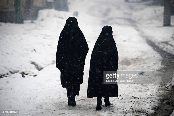Afghan gresidents walk along a street during snowfall in Kabul on February 19 2014 The Afghan capital has experienced its third snowfall of the...