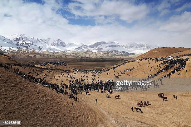 Afghan horsemen and spectators gather on an arid patch of land near snowcapped mountains to play the traditional sport of Buzkashi near Bamiyan city...