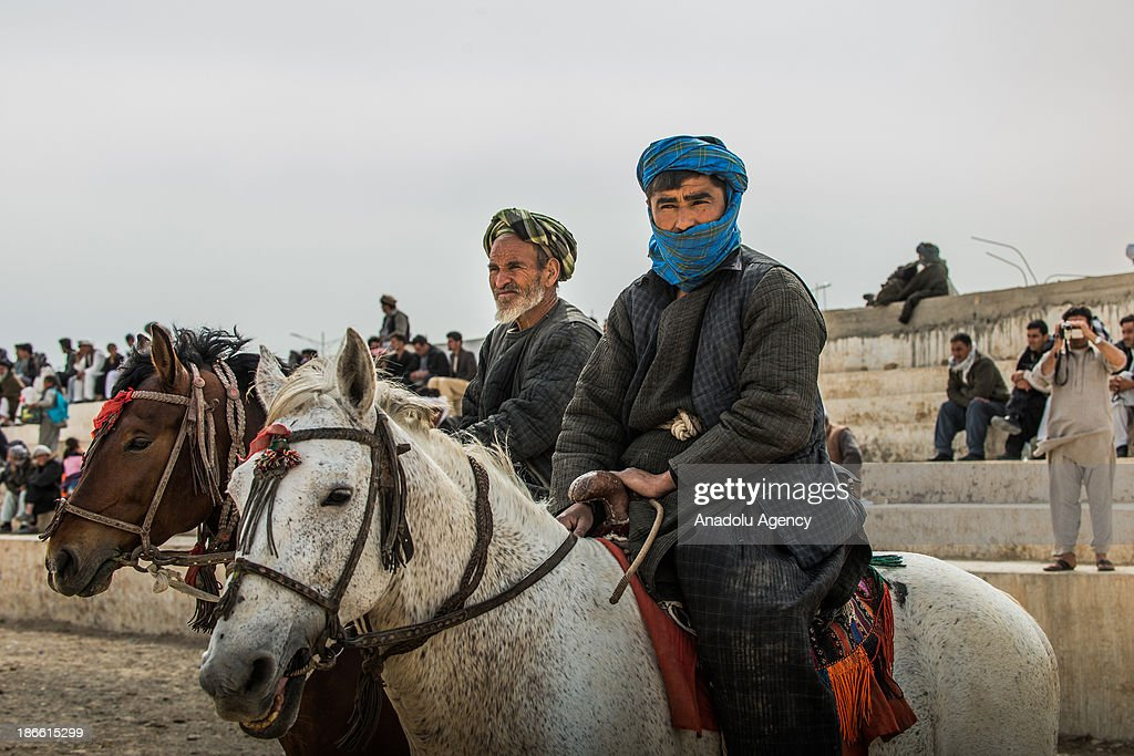 Afghan horsemen waiting before a game of Buzkashi in Mazar-i Sharif, Afghanistan. The ancient game of Buzkashi is an Afghan national sport which is played by two teams of horsemen competing to throw an animal (calf, goat or sheep) carcass into a scoring circle. The object of the game is to get control of the carcass and bring it to the scoring area.