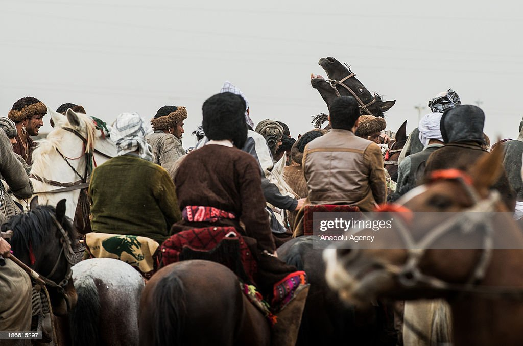 Afghan horsemen waiting in a line before a game of Buzkashi in Mazar-i Sharif, Afghanistan. The ancient game of Buzkashi is an Afghan national sport which is played by two teams of horsemen competing to throw an animal (calf, goat or sheep) carcass into a scoring circle. The object of the game is to get control of the carcass and bring it to the scoring area.