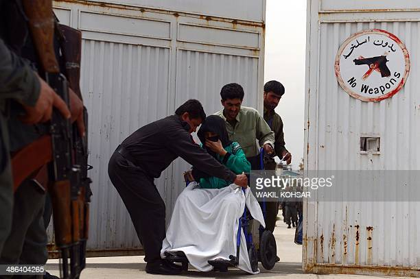 Afghan hospital attendants help a patient at the gate of the Cure Hospital in Kabul on April 24 2014 A guard shot dead three foreigners at a US...