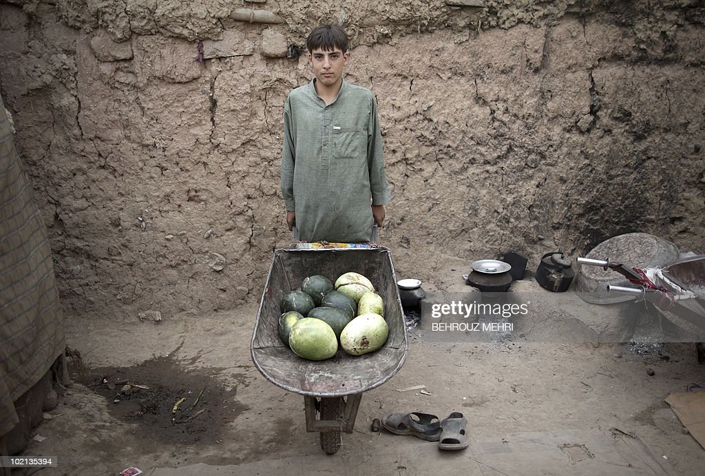 Afghan Hossein, an immigrant from Kunduz province of Afghanistan poses with watermelones in a wheelbarrow, bought for the family in a slum area in Islamabad on June 15, 2010. Pakistan approached the International Monetary Fund in 2008 and has secured a 11.3 billion USD standby loan in an effort to contain inflation and cope with a rapid depletion of reserves that were barely enough to cover nine weeks of import bills.