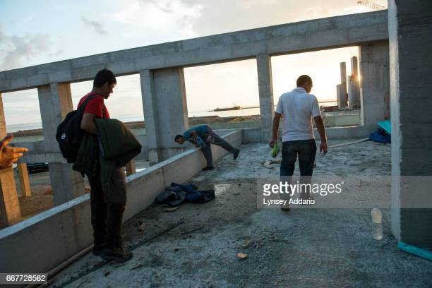 Afghan illegal migrants show off places they routinely sleep at an unfinished building at the port after a day of failed attempts to sneak onto...