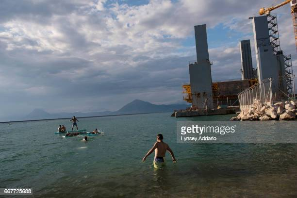 Afghan illegal migrants swim at the port after a day of failed attempts to sneak onto trucks at the port in Greece to enter Italy in Patras Greece...