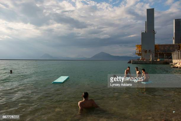 Afghan illegal migrants swim at the port and joke 'let's swim to Italy' after a day of failed attempts to sneak onto trucks at the port in Greece to...