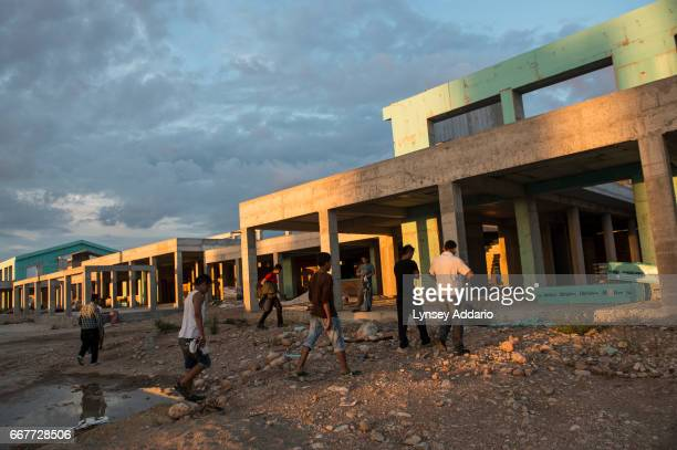 Afghan illegal migrants walk towards an unfinished building where several of them sleep at the port after a day of failed attempts to sneak onto...