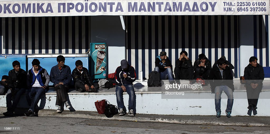Afghan immigrants rest in front of a store hours after they landed on the island of Lesbos' northern coast in Mantamados, Greece, on Saturday, Dec. 8, 2012. In recent months, Lesbos has become a hot spot for migrants as Greece struggles to cope with waves of refugees from Middle Eastern conflict even as it reels from economic crisis at home. Photographer: Kostas Tsironis/Bloomberg via Getty Images