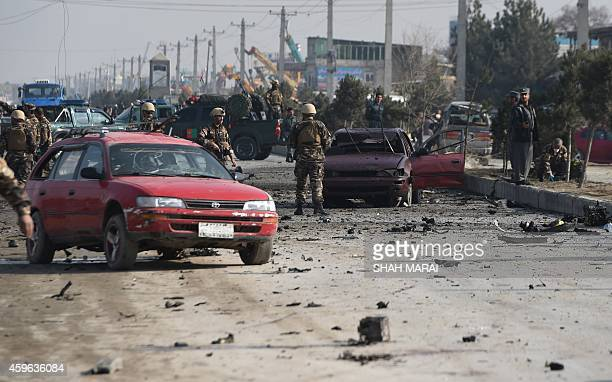 Afghan intelligence personnel inspect the site of a suicide attack on a British embassy vehicle along the KabulJalalabad road in Kabul on November 27...