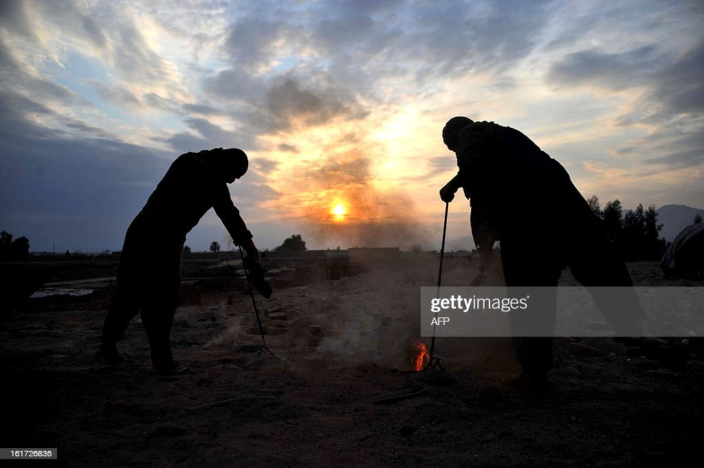 Afghan labourers add coal to the fire at a traditional brick factory on the outskirts of Jalalabad on February 14, 2013. Over a third of Afghans are living in abject poverty, as those in power are more concerned about addressing their vested interests rather than the basic needs of the population, a UN report said. AFP PHOTO/ Noorullah Shirzada