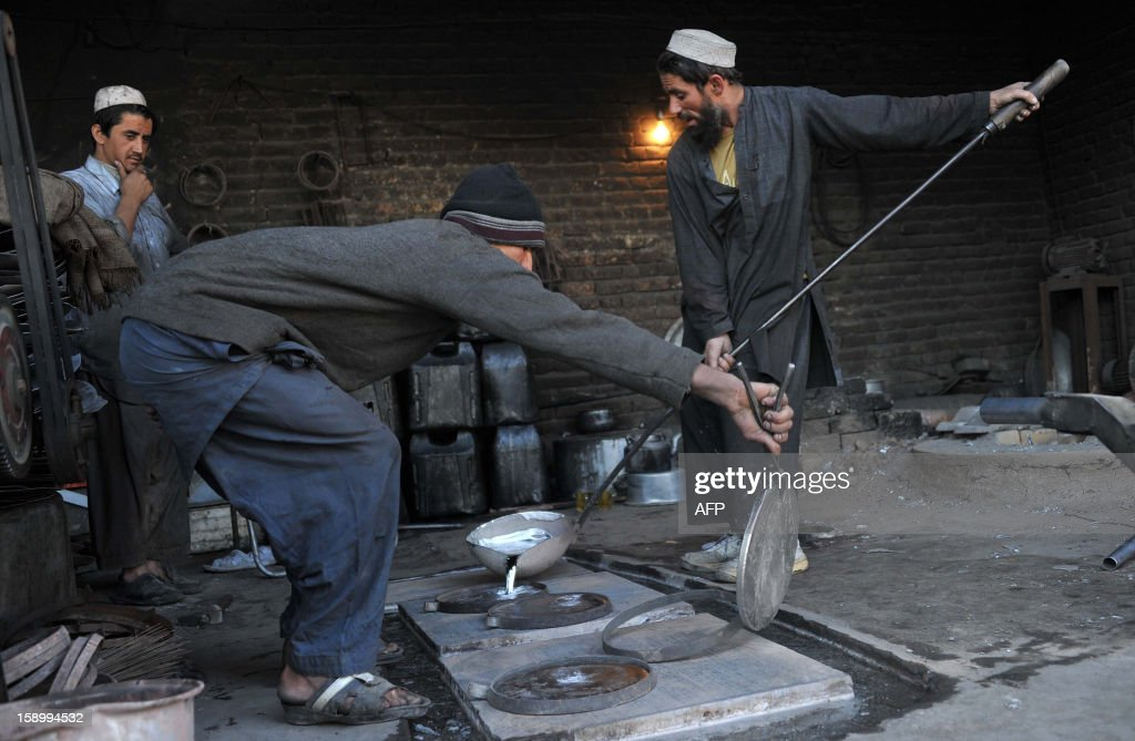 Afghan labourers pour melted aluminium at a factory that produces pots on the outskirts of Jalalabad on January 5 ,2013. Over a third of Afghans are living in abject poverty, as those in power are more concerned about addressing their vested interests rather than the basic needs of the population, a UN report said. AFP PHOTO/ Noorullah Shirzada