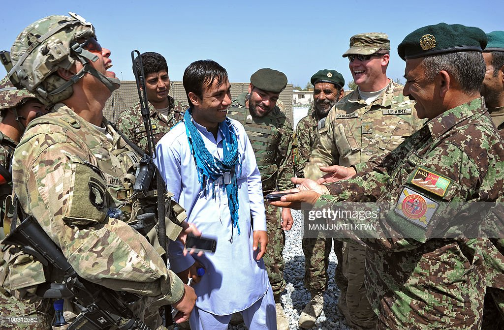 Afghan Lieutenant Colonel from the 201st Selab, 4th Brigade, 4th Battalion, Afghanistan National Army (ANA), Asadullah (R), and US Captain Leonguerrero (L) from the Field Artillery Battery of 4th Kandak, 4th Brigade, 201st Corps of Combined Team Bastogne (Nangarhar), 101st Airborne Division share a light moment during a training session of ANA soldiers in artillery use at Forward Base Shinwar in the province of Nangarhar on April 11, 2013. US-led coalition forces are winding down their operations before a scheduled withdrawal of the bulk of their 100,000 troops by the end of 2014, and racing to prepare Afghan forces to take over responsibility for security. AFP PHOTO/ Manjunath KIRAN