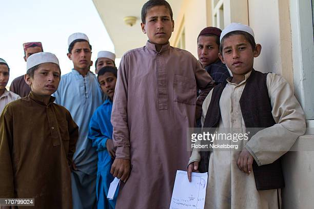 Afghan males wait outside a government clinic for their drug prescriptions to be filled May 14 2013 on the eastern outskirts of Kabul Afghanistan The...