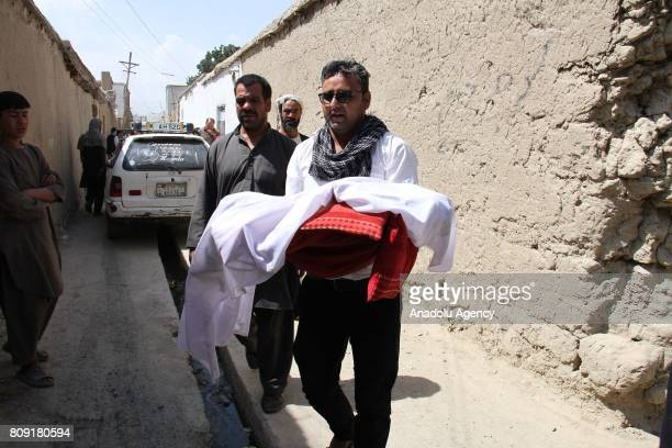 Afghan man carries body of a child after rockets hit their house in Afghanistans capital Kabul Afghanistan on July 5 2017