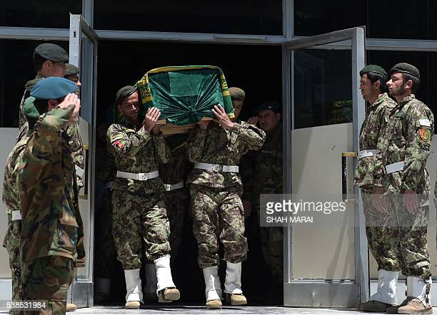 Afghan members of a guard of honor carry the coffin of Afghan reporter Zabihullah during a ceremony at a military hospital in Kabul on June 7 2016...