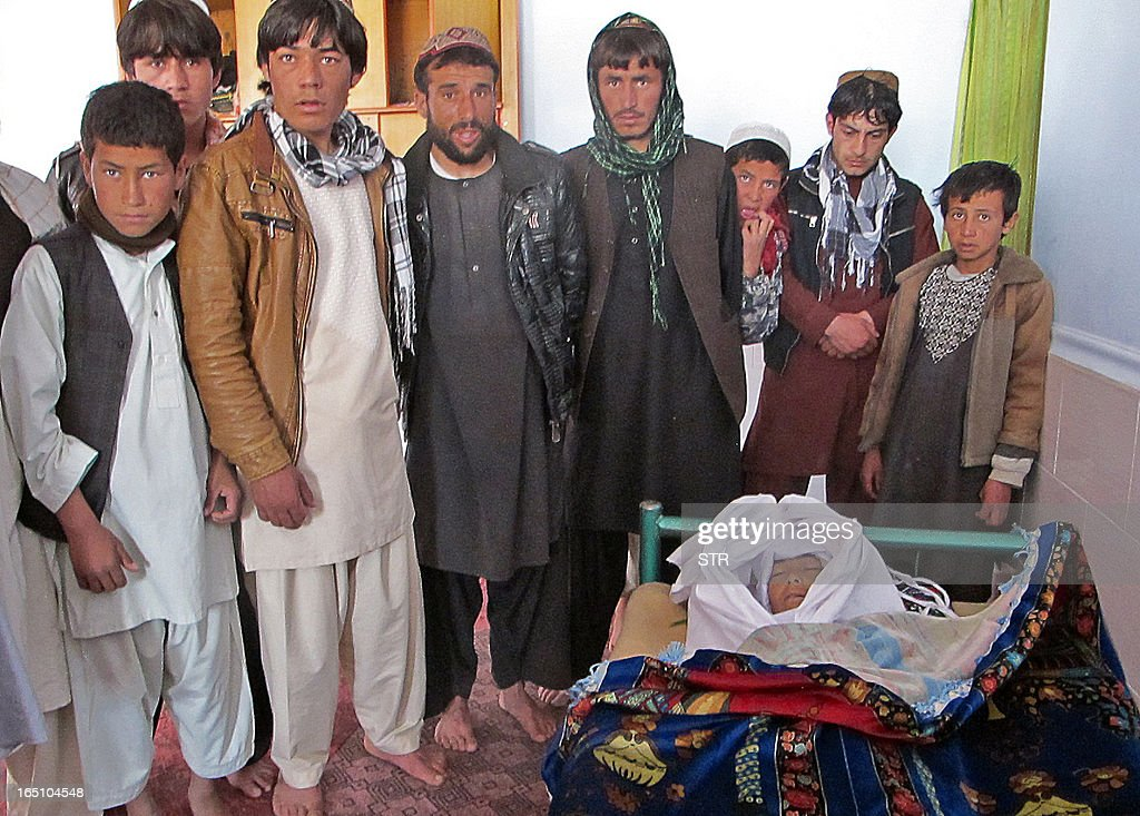 Afghan men and children stand near the dead body of a boy who was allegedly killed during a NATO helicopter strike on the outskirts of Ghazni on March 30, 2013. A NATO helicopter strike killed two children in south Afghanistan on Saturday, officials said, in the latest civilian casualities to beset the coalition's war against Taliban militants.