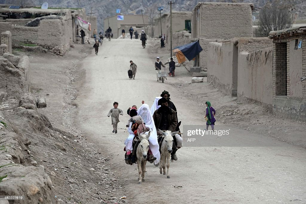 Afghan men and women ride on donkeys through the centre of a village in Kishindih district of northern Balkh Province on April 3 2014 Afghans will go...