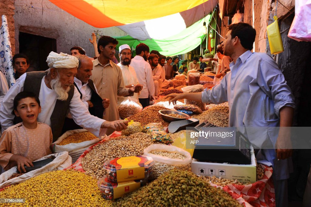 Afghan men buy dry fruits and sweets for the Eid festival, which marks the end of the Muslim holy month of Ramadan, at a market in Herat on August 5, 2013. Afghan Muslims, like millions of Muslims around the world, are observing the holy month of Ramadan - a month of fasting and spiritual purity during which they refrain from eating, drinking or sex from dawn until dusk. AFP PHOTO/ Aref KARIMI