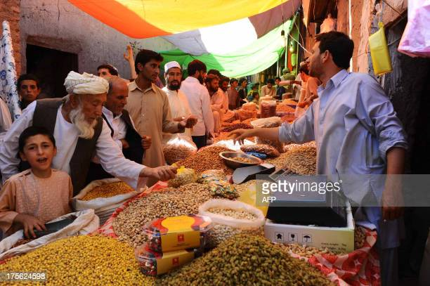 Afghan men buy dry fruits and sweets for the Eid festival which marks the end of the Muslim holy month of Ramadan at a market in Herat on August 5...