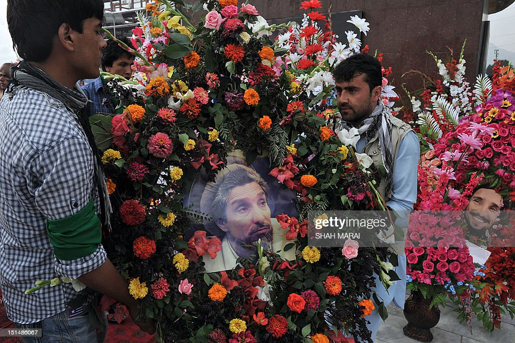 Afghan men carry a floral wreath in memory of slain Afghan national hero Ahmad Shah Massoud during a ceremony marking the eleventh anniversary of his death in Kabul on September 8, 2012. Massoud, nicknamed the 'Lion of the Panjshir' for his armed struggle against the Taliban that ruled Afghanistan at the time, died September 9, 2001 when two Tunisians posing as journalists with fake Belgian passports detonated a bomb hidden in the camera as they pretended to interview him. His death, just two days before the September 11 attacks in New York and Washington, has been linked to Osama bin Laden's al-Qaeda network by US officials. AFP PHOTO/ SHAH Marai